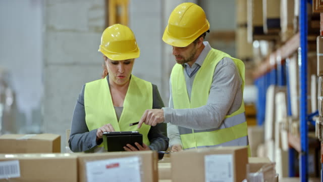 Male and female warehouse employee doing an inventory check in the warehouse video