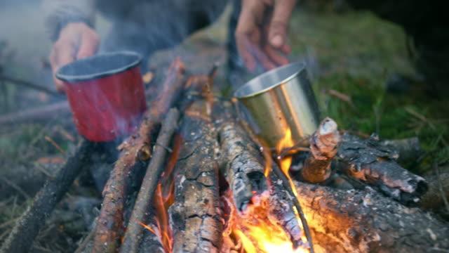 männliche und weibliche wildnis überleben experte trinken tee, während am lagerfeuer sitzen - camping stock-videos und b-roll-filmmaterial
