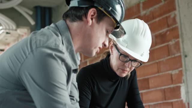 männliche architekt und ingenieurin überprüfen die details auf dem plan auf der baustelle - kopfbedeckung stock-videos und b-roll-filmmaterial