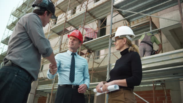 Male architect and female engineer shaking hands with project manager at the construction site video