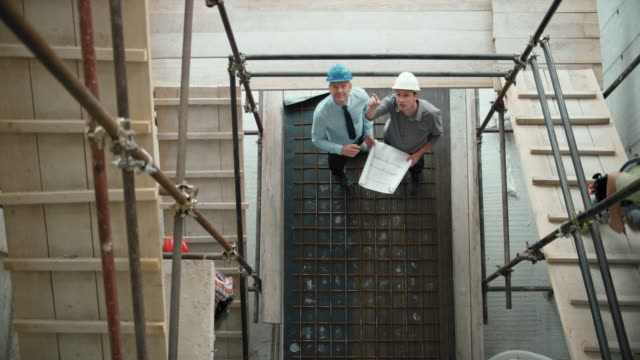 LD Male architect and male project manager discussing construction progress standing at the bottom of the scaffold staircase at the construction site video