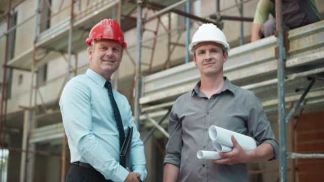 Male architect and project manager shaking hands at the construction site Medium handheld shot of a male architect and project manager talking at the construction site and shaking hands. Shot in Slovenia. work helmet stock videos & royalty-free footage
