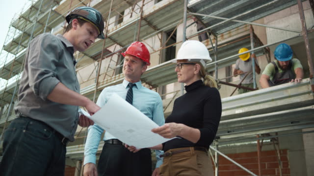 Male architect, female engineer and the project manager talking at the construction site while holding the plans in their hands video