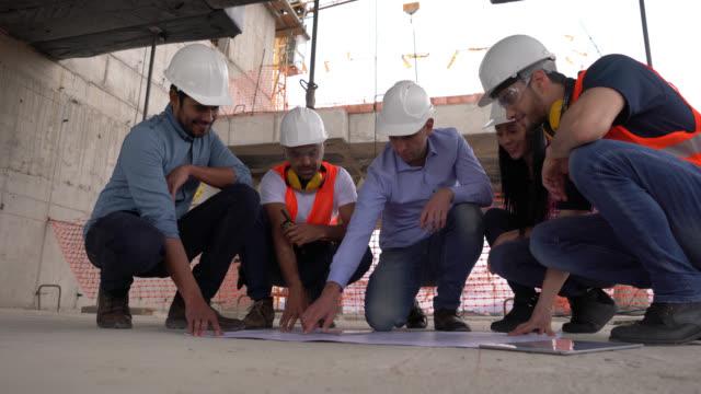 manliga arkitekt att ge instruktioner till hans team alla knä på golvet medan du tittar på en plan - construction workwear floor bildbanksvideor och videomaterial från bakom kulisserna