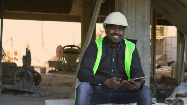 Male architect holding digital tablet at site Portrait of Indian male engineer holding digital tablet at construction site. Smiling architect is sitting on planks. He is wearing protective workwear. manual worker stock videos & royalty-free footage