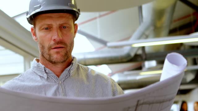 männliche architekten betrachten blaupause 4k - reliability stock-videos und b-roll-filmmaterial