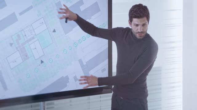 manliga arkitekt visar plan detaljer till sina kolleger på en widescreen-skärm i konferensrummet - man architect computer bildbanksvideor och videomaterial från bakom kulisserna