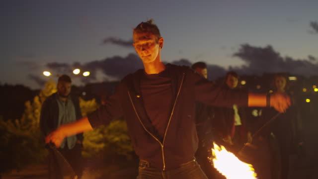 vídeos de stock, filmes e b-roll de artista masculino realizando show de fogo ao ar livre em vez de noite. - artista