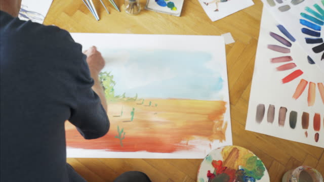 Male artist working on painting in studio. video