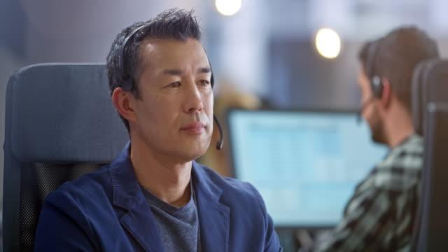 カスタマーサポートを提供しながら笑顔のアジアのコールセンターエージェントの男性 - オペレーター 日本人点の映像素材/bロール