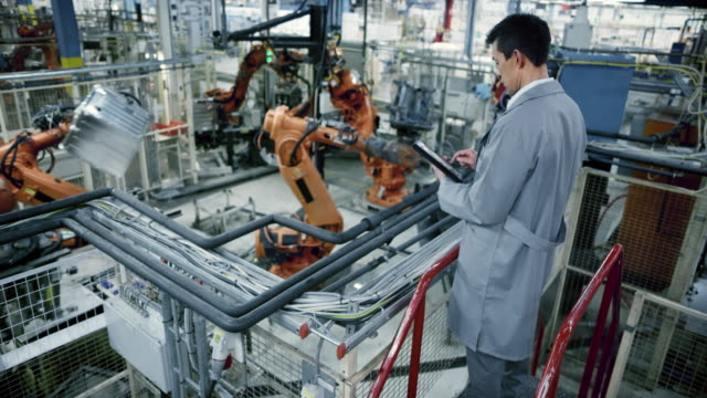 ld male asian engineer inspecting the work process of the robots performing their operations in the factory - деятельность стоковые видео и кадры b-roll