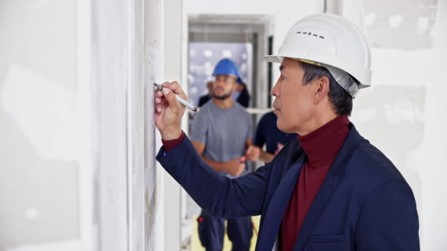 PAN Male Asian interior architect making sketches on the whiteboard at the building site
