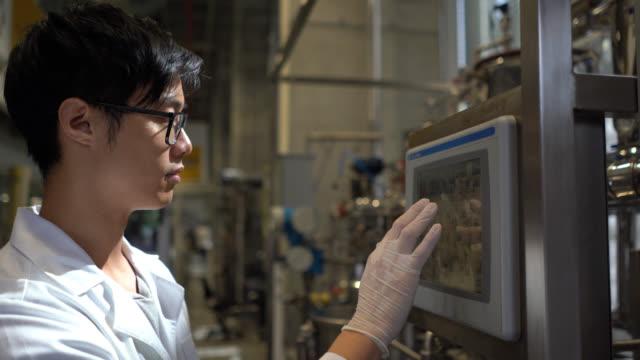stockvideo's en b-roll-footage met mannelijke aziatische student werkzaam bij het proceslab distilleren vloeistoffen - chemische fabriek