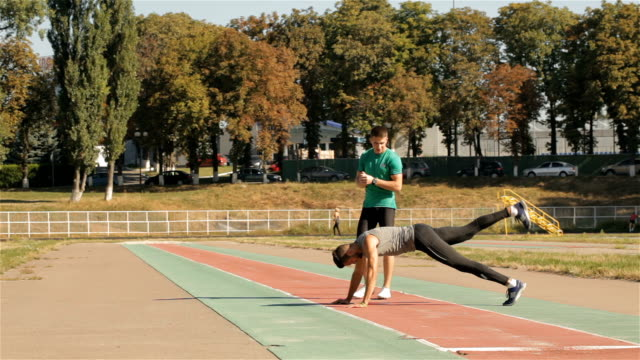 Male athlet pushes up from the ground Caucasian male athlet pushing up from the ground. Young sportsman alternately lifting his legs in face to ground position. Two fit guys dressed in sport wear going away by the track bodyweight training stock videos & royalty-free footage