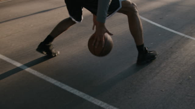 male athlete dribbling ball on basketball court - agilità video stock e b–roll