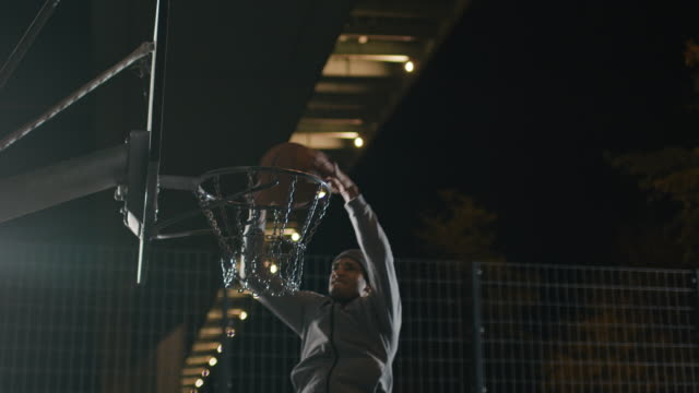 Male athlete dunking basketball in hoop at night
