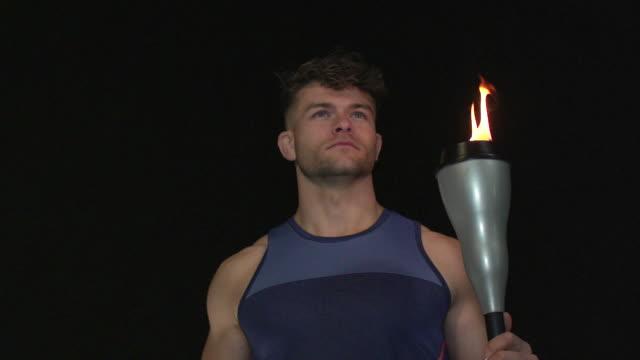 männliche athleten halten flammende fackel - super slow motion 180-grad-rotation - fackel stock-videos und b-roll-filmmaterial