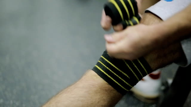 male athlete in the sport shoes 30 years of age rewinds his knee on the leg hair sport athletic bandage black with yellow stripes, for Security, to load on the joint video