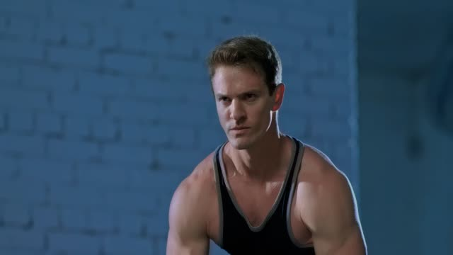 manlig idrottsman tränar i gymmet, musklerna fungerar, en vacker torso. idrottsman andas under övningar, gör övningar på musklerna i armar och rygg. stående vy. - människorygg bildbanksvideor och videomaterial från bakom kulisserna