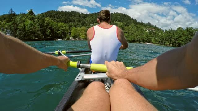 vídeos de stock, filmes e b-roll de atleta masculino pov remo atrás de seu companheiro de equipe um lago ensolarado - remo esporte aquático