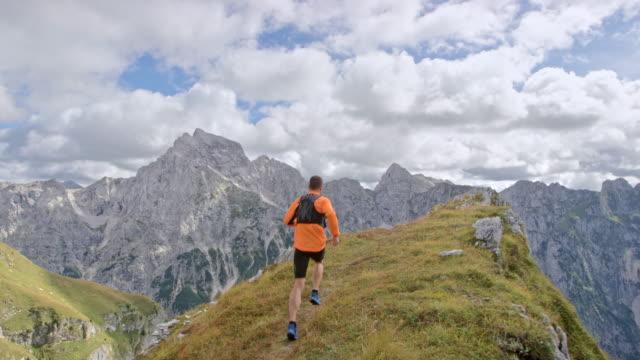 slo mo mężczyzna sportowiec działa na skraju grzbietu górskiego z zapierającym dech w piersiach widokiem - mountain top filmów i materiałów b-roll
