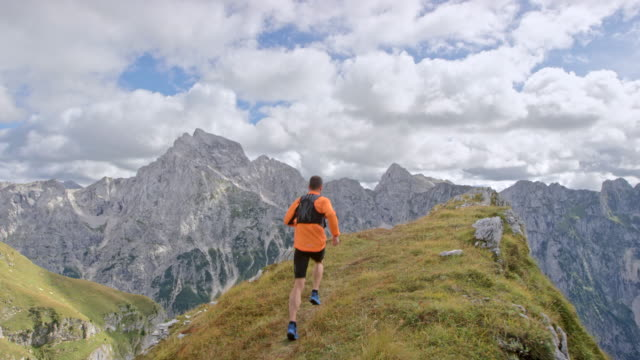 slo mo 남자 선수의 경치와 산 능선의 가장자리에 실행 - mountain top 스톡 비디오 및 b-롤 화면