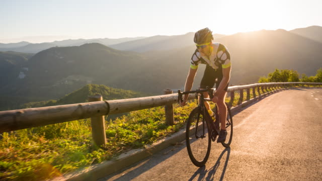 male athlete standing while road cycling uphill - ciclismo su strada video stock e b–roll