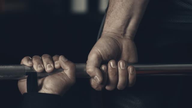 支援とジムで体重を持ち上げる男性アスリート取ってバー - 支えられた点の映像素材/bロール