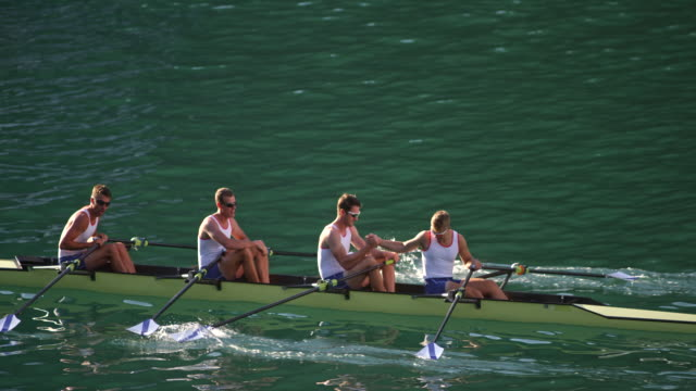 SLO MO hombre atletas en una cuádruple scull en un lago estrechándole la mano - vídeo