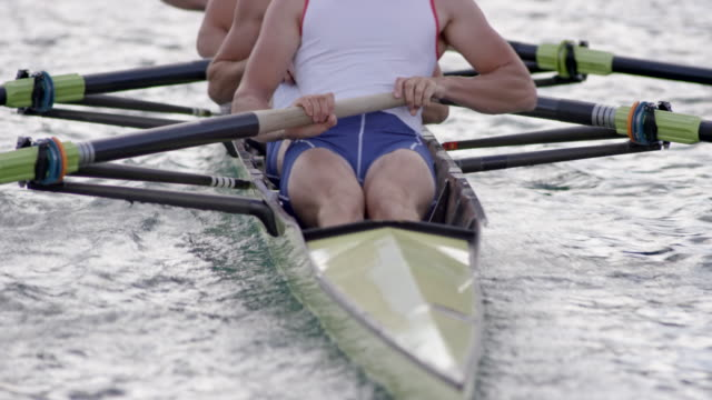 Male athletes rowing in a coxless four video