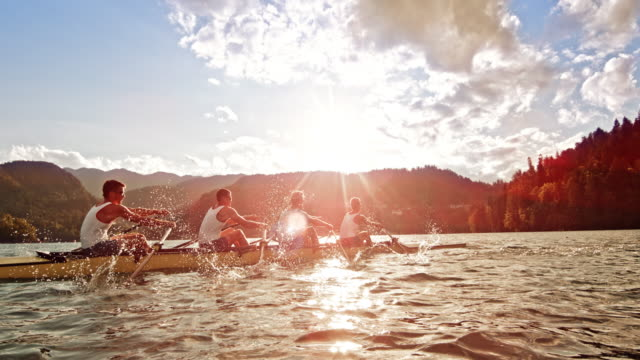 SLO MO Male athletes rowing on a lake in sunshine video