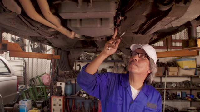 Male auto mechanic inspects the car undercarriage way in garage, car service concept. dolly shot video