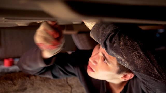 ガレージ内のコンポーネントをねじ込む車の下に男性の自動車整備士 ビデオ