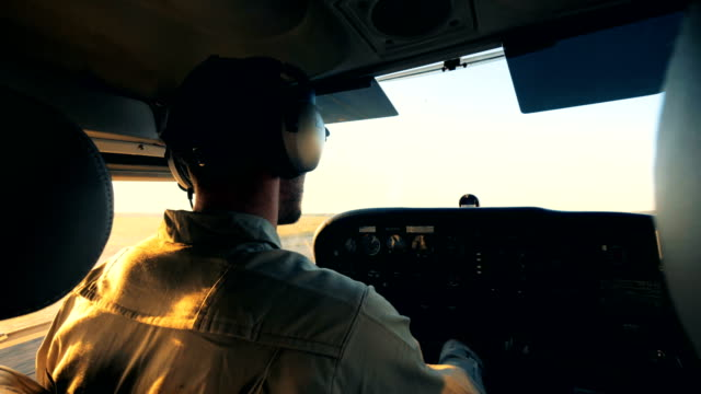 Male aviator piloting an airplane, back view. A man sits in a cockpit, riding a biplane on an airfield. propeller airplane stock videos & royalty-free footage