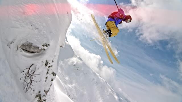 slo mo男性バックカントリースキーヤーは岩から飛び降りる - エクストリームスポーツ点の映像素材/bロール
