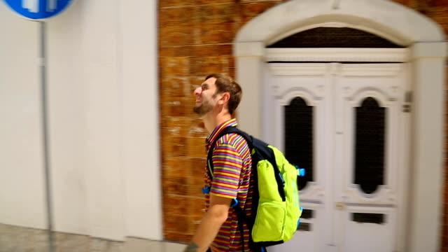 erkek backpacker kasabanın dar sokakta yürürken parlak güneşli bir günde, tatil - sırt çantalılar stok videoları ve detay görüntü çekimi