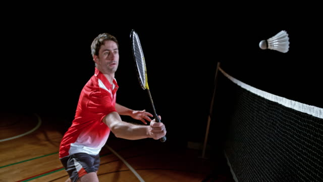 SLO MO Male badminton player in a red shirt hitting the shuttlecock video