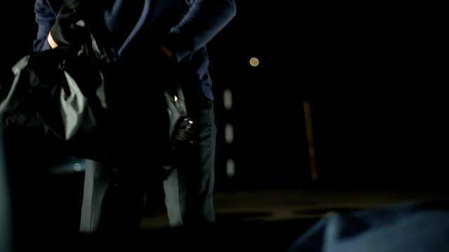 vídeos de stock e filmes b-roll de male bandit opening car trunk and throwing moneybag, bank robbery crime - roubar crime