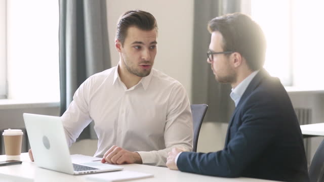 Male bank manager or investment advisor consulting client with laptop Male professional bank manager investment advisor consulting customer with laptop offering contract at business meeting, insurer broker explain loan insurance deal talking giving papers to client salesman stock videos & royalty-free footage