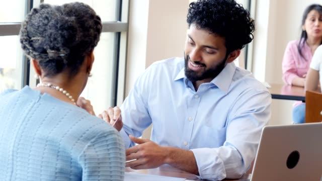 il rappresentante della banca maschile parla con il cliente femminile - conto corrente video stock e b–roll