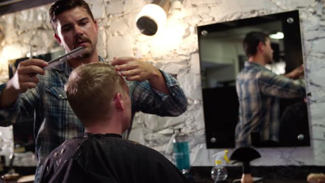 männliche friseur haarschnitt für kunden in-shop - friseur lockdown stock-videos und b-roll-filmmaterial