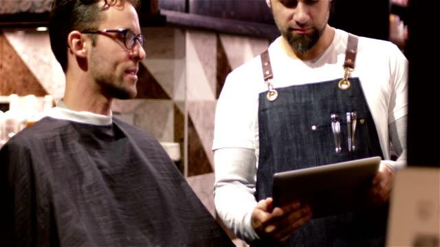 男性理容室顧客にデジタル タブレットの表示 - 美容室のビデオ点の映像素材/bロール
