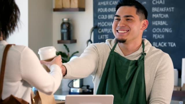 eine männliche barista hände ein kunde ihren kaffee als er lächelt und spricht mit ihr. - barista stock-videos und b-roll-filmmaterial