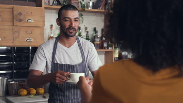 Male barista serving coffee to the customer at counter Close-up of smiling male barista in apron serving coffee to the female customer at counter in cafe wait staff stock videos & royalty-free footage