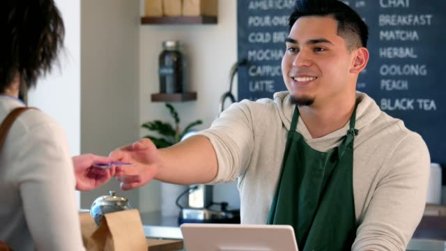 A male barista takes the order of a woman who holds out her credit card to pay. A young, male barista tells a female customer her total. She then hands him her card and watches as he swipes it. He hands the card back before giving her the drink with a smile, and asking her another question. wait staff stock videos & royalty-free footage