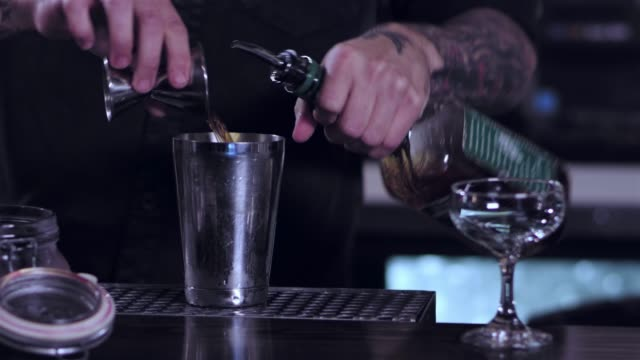male bartender pouring liquid into a cocktail shaker in order to prepare an alcoholic drink at a bar - bicchiere vuoto video stock e b–roll