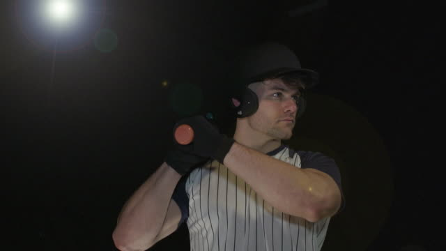 Male Baseball Player Portrait pose - Super Slow Motion 180 degree rotation Stock HD video clip footage of a male Baseball Player. Filmed in Super Slow motion, the camera rotates 180 degrees around the player. Black Background. Indoors pre game stock videos & royalty-free footage