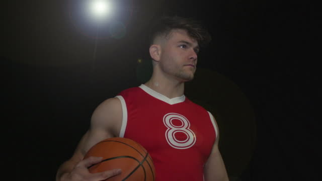 Male Basketball Player Portrait pose - Super Slow Motion 180 degree rotation Stock HD video clip footage of a male Basketball Player. Filmed in Super Slow motion, the camera rotates 180 degrees around the player. Black Background. Indoors pre game stock videos & royalty-free footage