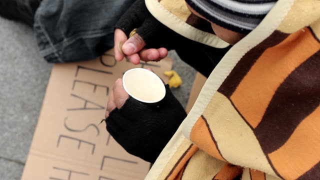 Male beggar counting money and putting in paper cup, sadness and poverty video