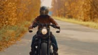 istock Male biker in glasses and a helmet rides a cool motorcycle in the fall along the highway. Portrait view. 1181500122